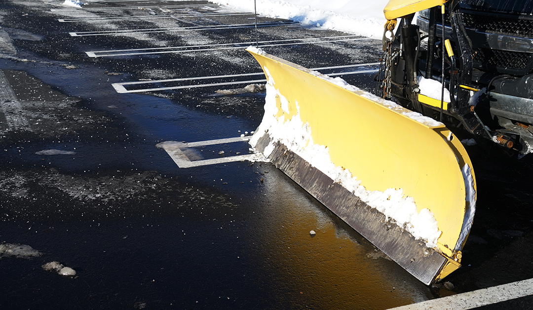Snowplow in the parking lots with snow removed